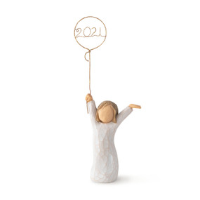 Front view, standing girl figure in cream dress, holding gold wire balloon with 2021 written in gold wire inside balloon