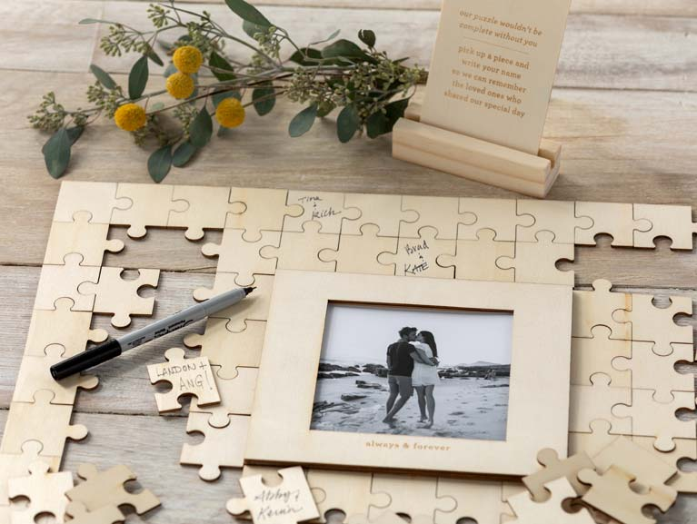 Wooden puzzle surrounding a wedding picture. Handwritten messages are on some of the puzzle pieces.