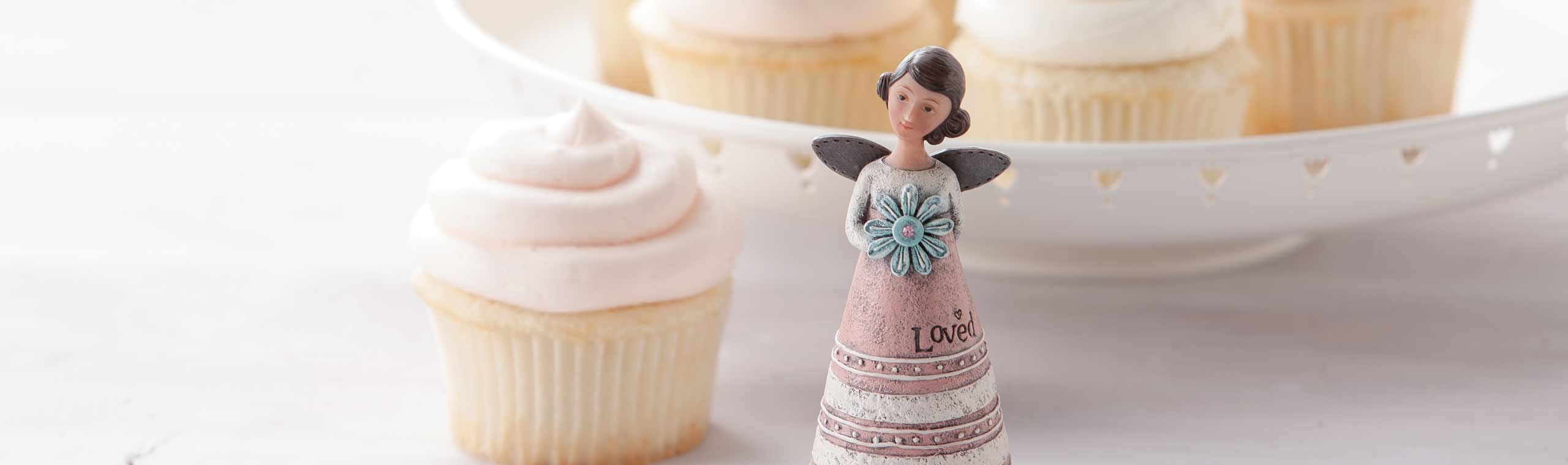 Angel with a birthstone setting in front of cupcakes