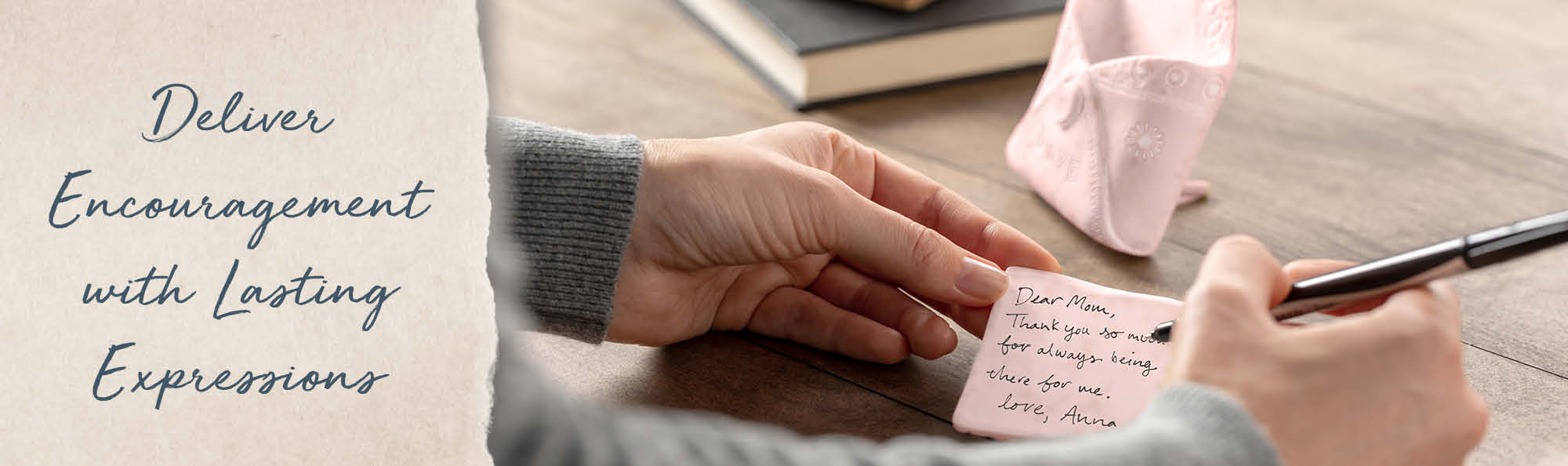Deliver encouragement with Lasting Expressions. Woman writing a note on a card.