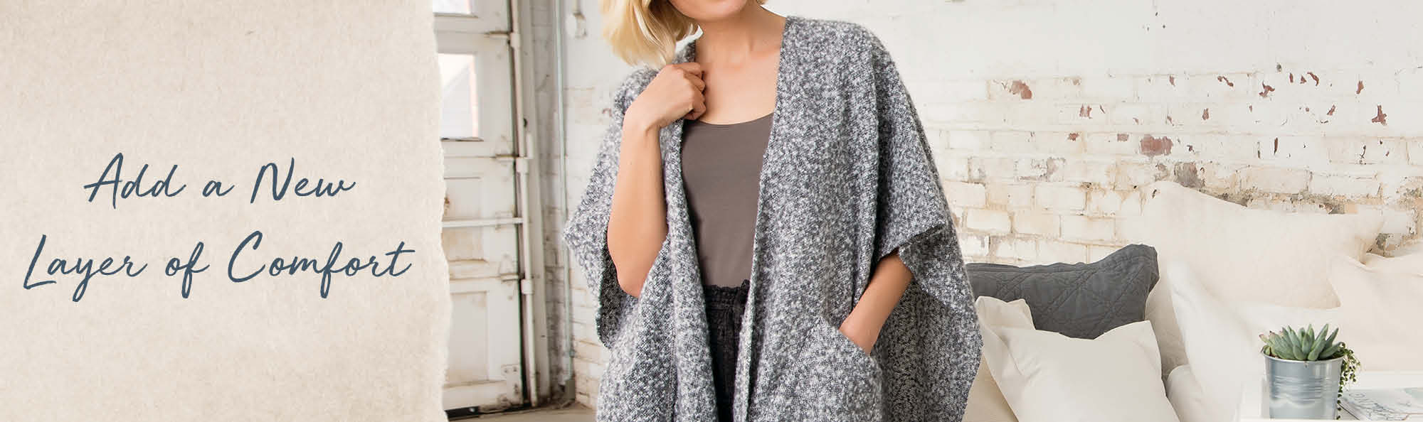 Add a new layer of comfort. Woman wearing a gray robe over her shoulders.