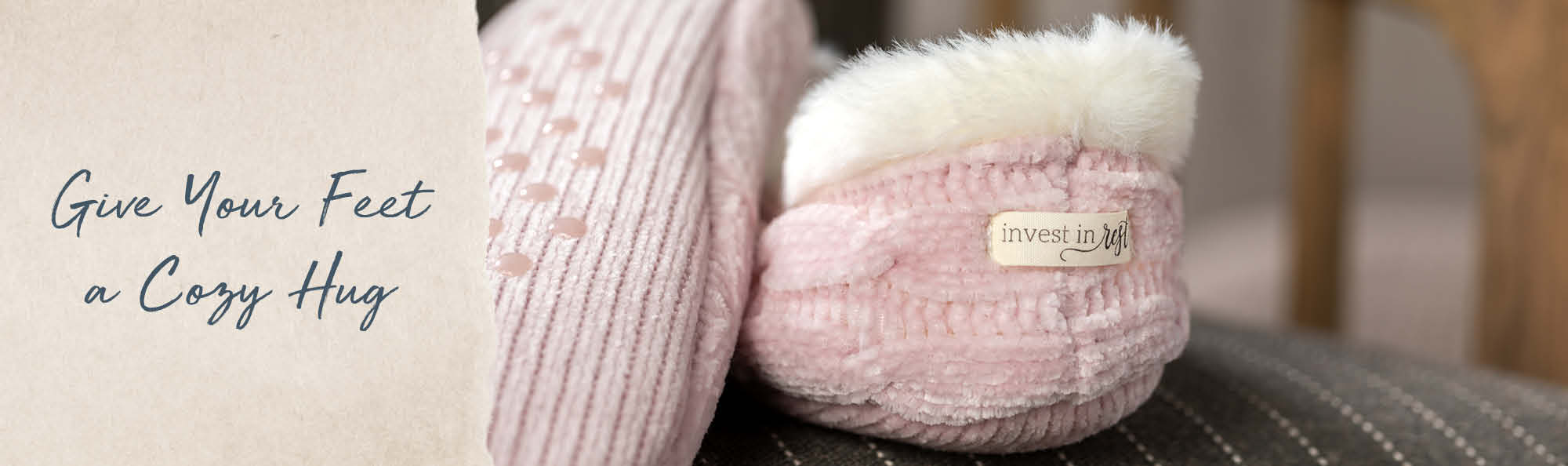 Give Your Feet a Cozy Hug. Soft pink slippers with a tag that reads Invest in Rest.