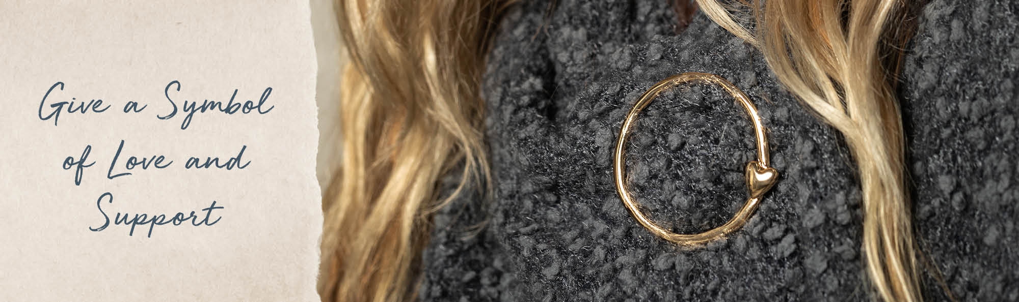 Give a Symbol of Love and Support. Gold circle pinned on to a soft gray shawl.