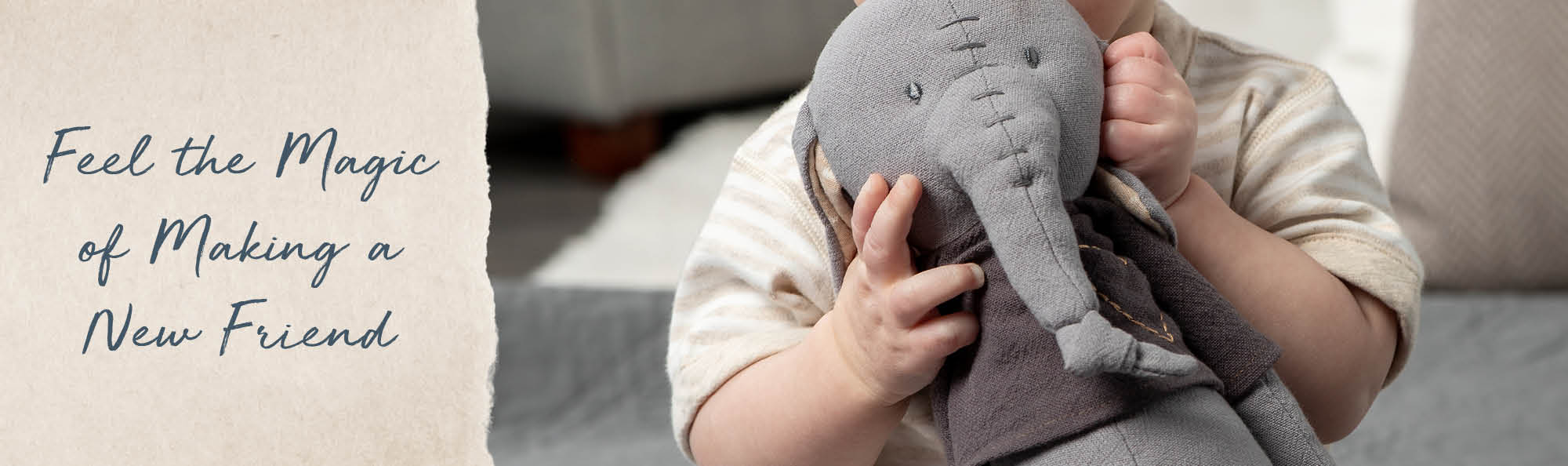 Feel the magic of creating a new friend. Baby holding a stuffed elephant with hand-stitched details.