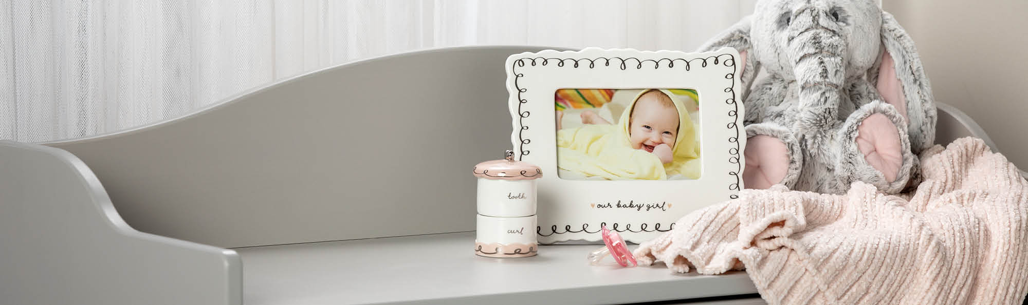 Frame, Tooth Box, Stuffed Elephant, and soft blanket setting on a white dresser