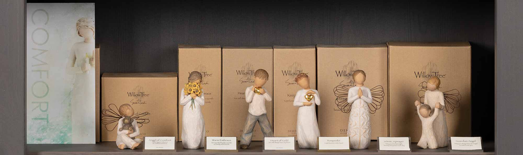 Willow Tree hand carved figures displayed on a store shelf with a sign that says COMFORT