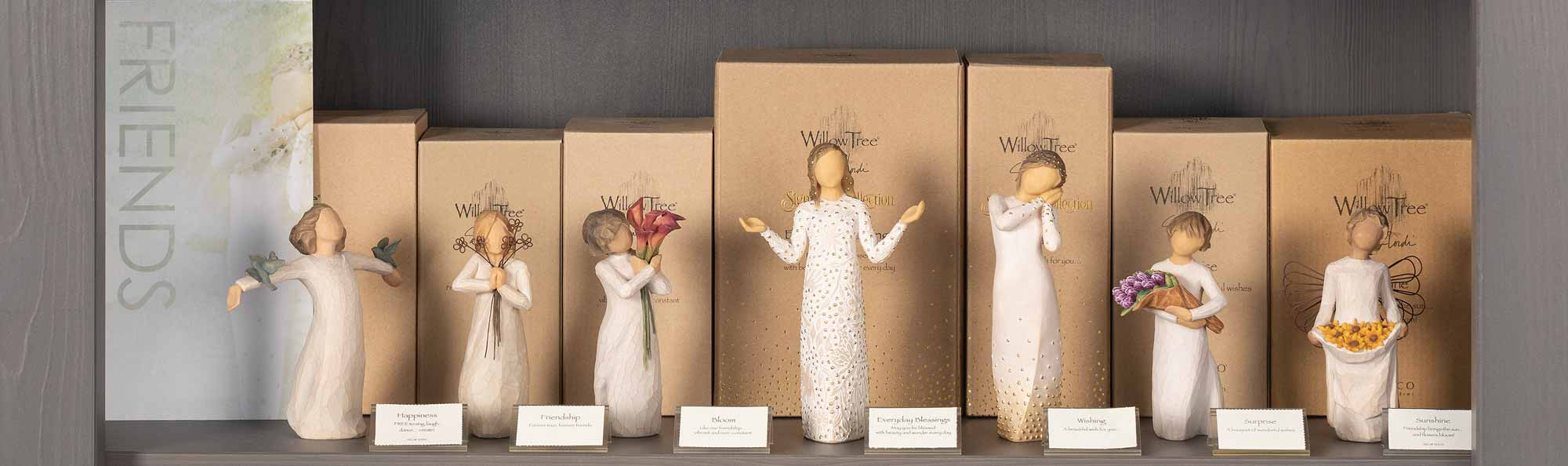 Willow Tree hand carved figures displayed on a store shelf with a sign that says FRIENDS