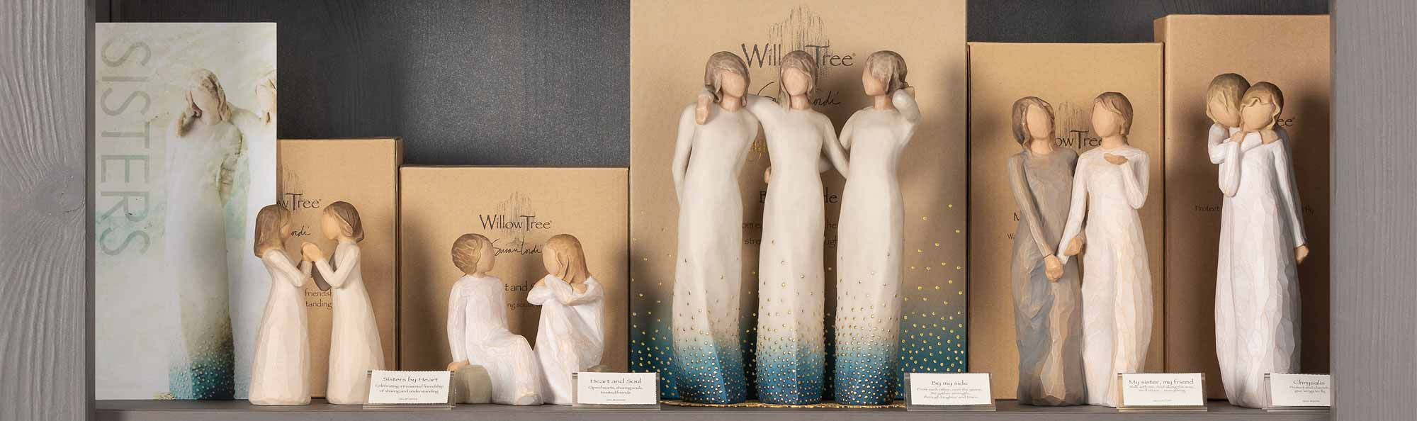 Willow Tree hand carved figures displayed on a store shelf with a sign that says SISTERS