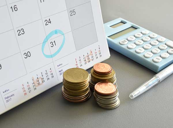 Calendar, stacks of coins, pencil, and calculator