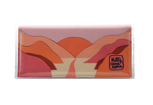 This is an image of the front of a Kitty Came Home bifold plus purse clutch in 'The golden dawn' design by Satin and Tat. A path wends through a valley of pink and orange hills towards a rising orange sun.