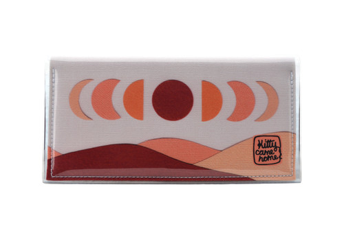 This is an image of the front of a Kitty Came Home bifold plus purse clutch in 'The same moon shines' design by Satin and Tat. The moon appears in all its phases in a white sky above a landscape lit by the moon's colours: burgundy, oranges, and apricot. This is the large size.