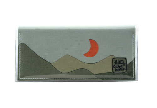 This is an image of the Front of a Kitty Came Home bifold plus purse clutch of the 'Moondance' design by Satin and Tat. An orange crescent moon floats above a landscape of dark green hills. This is the large size.