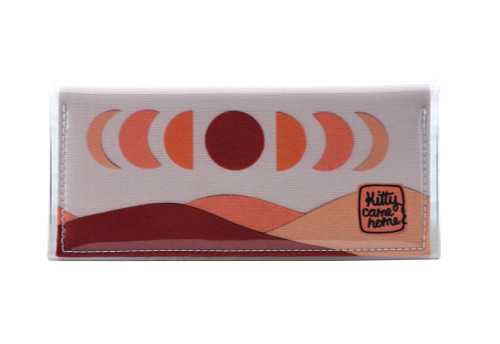 This is an image of the front of a Kitty Came Home bifold purse clutch in 'The same moon shines' design by Satin and Tat. The moon appears in all its phases in a white sky above a landscape lit by the moon's colours: burgundy, oranges and apricot. This is the standard size.