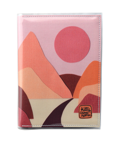 This is an image of the front of a Kitty Came Home A5 journal in the 'Lily of the valley' design by Satin and Tat. A pink sun in a dusty pink sky above a landscape of orange, pink, burgundy and magenta hills. A path leads between the hills toward the distant mountains.