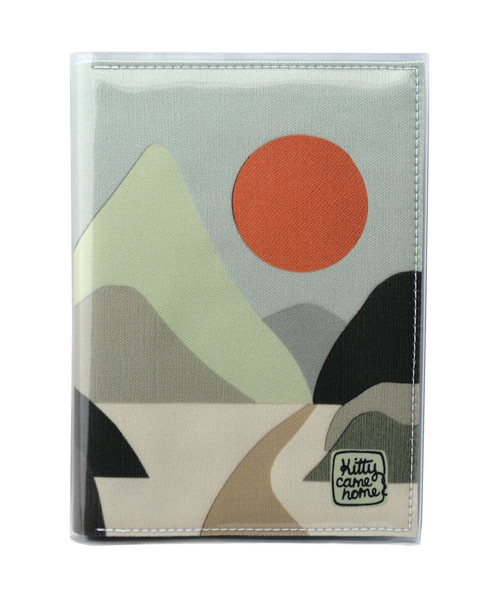 This is an image of the front of a Kitty Came Home A5 journal in the 'Moonlight drive' design by Satin and Tat. An orange sun in a pale green sky above a landscape of green hued hills. A path leads between the hills toward the distant mountains.