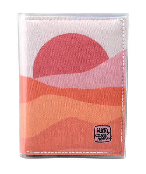 This is an image of the front of a Kitty Came Home A5 journal in the 'Waiting for the sun' design by Satin and Tat. A warm pink sun rises over a landscape of pink hued sands.