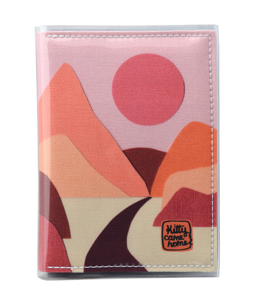 This is an image of the front of a Kitty Came Home A6 journal in the 'Lilly of the valley' design by Satin and Tat. A pink sun in a dusty pink sky above a landscape of orange, pink, burgundy and magenta hills. A path leads between the hills toward the distant mountains.