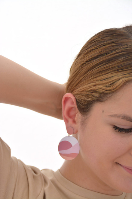 The image shows a woman wearing a Kitty Came Home large circle drop stud earring in her right ear. The top stud is 12 millimetre in diameter and the lower dangle circle is 36 millimetre in diameter. The design is waiting for the sun by Satin and Tat. Pale pink and orange forms create a landscape of rolling hills beneath a terracotta sun rising into a pale pink sky.
