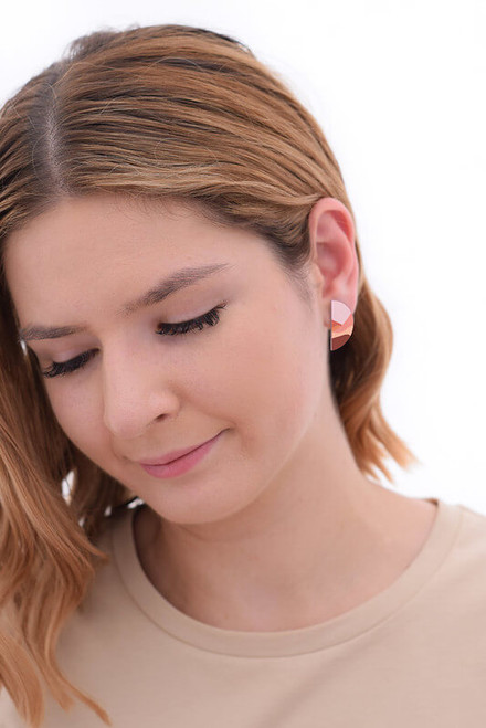 This image shows a woman wearing a Kitty Came Home stud earring in her left ear. The semi circle shape is 25 millimetres in diameter. The design is called lily of the valley by Satin and Tat. A landscape of gently rolling hills in terracotta colours lays beneath a pale pink sky.