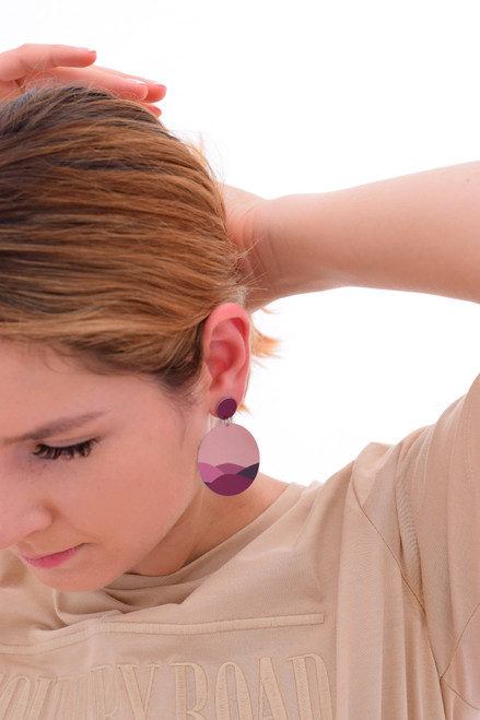 This image shows a woman wearing a Kitty Came Home drop stud earring in her left ear. The top circle is 12 millimetres in diameter and the dangle circle is 36 millimetres in diameter. The design is called moonage daydream by Satin and Tat. Burgundy shapes form a landscape of gently rolling hills beneath a warm pink night sky.