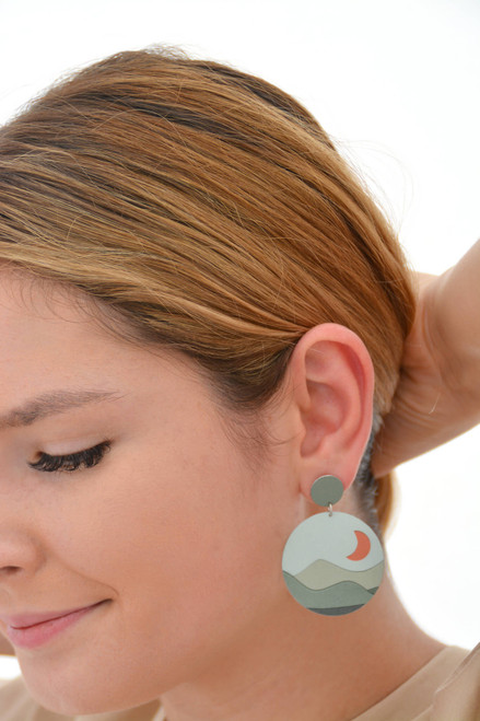 This is an image of a woman wearing a Kitty Came Home drop stud earring in her left ear. The top circle is 12 millimetres in diameter and the dangle circle is 36 millimetres in diameter. The design is called moondance by Satin and Tat. An orange crescent moon floats in a pale green sky above a landscape of gently rolling green hills.