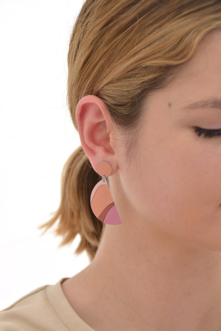 This is an image of a woman wearing a Kitty Came Home drop stud earring in her right ear. The top circle is 12 millimitres in diameter and the dangling semi circle beneath is 36 millimetres in diameter. The design is called the golden dawn by Satin and Tat. Burgundy, orange and terracotta shapes form a landscape of gently rolling hills beneath an orange-pink sky.