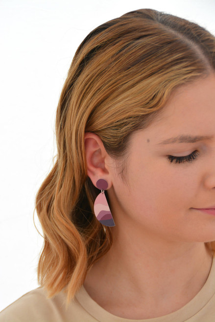 This is an image of a woman wearing a Kitty Came Home drop stud earring in her right ear. The top circle is 12 millimitres in diameter and the dangling semi circle beneath is 36 millimetres in diameter. The design is called the night comes down by Satin and Tat. Magenta and burgundy shapes form a landscape of gently rolling hills beneath a dusty pink sky.