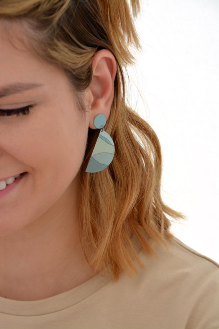 This is an image of a woman wearing a Kitty Came Home drop stud earring in her left ear. The top circle is 12 millimetres in diameter and the dangling semi circle is 36 millimetres in diameter. The design is the night grows pale by Satin and Tat. A landscape of gentle rolling hills in differing greens lies beneath a pale green sky.