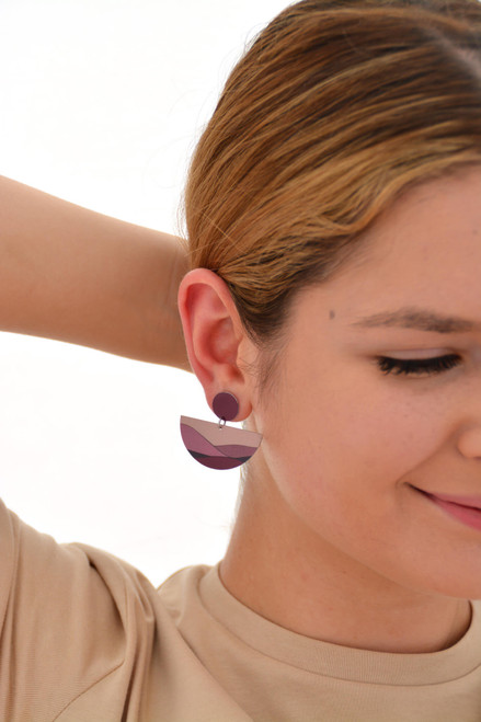 This is an image of a woman wearing a Kitty Came Home drop stud earring in her right ear. The top circle is 12 millimitres in diameter and the dangling semi circle beneath is 36 millimetres in diameter. The design is called moonage daydream by Satin and Tat. Magenta and burgundy shapes form a landscape of gently rolling hills beneath a terracotta sky.