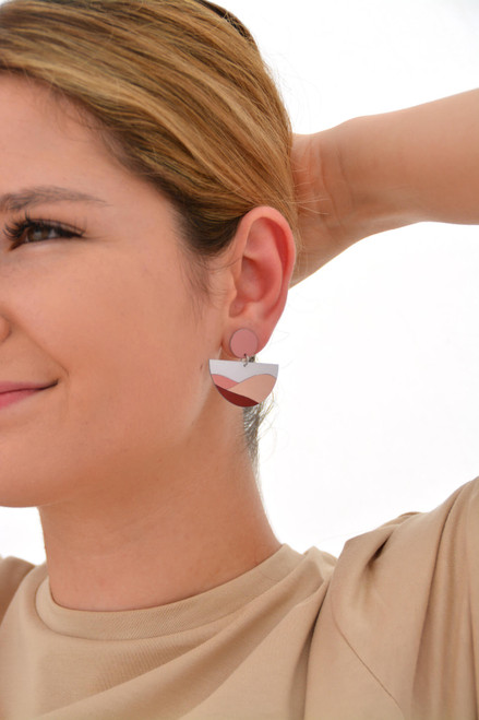 This is an image of a woman wearing a Kitty Came Home drop stud earring in her left ear. The top circle is 12 millimetres in diameter and the semi circle dangle is 36 millimetres in diameter. The design is the same moon shines by Satin and Tat. Burgundy and terracotta shapes form a gently undulated landscape beneath a clear white sky.