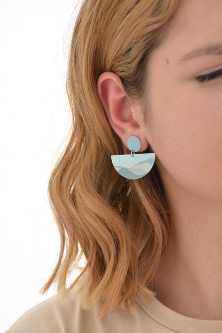 The image shows a woman wearing a Kitty Came Home double drop stud semi-circle earring in her right ear. The top stud is a 12 millimetre diameter circle, and the lower dangle is a 36 millimetre diameter semi-circle. The design is The Night Grows Pale by Satin and Tat. Pale blue and green forms create a landscape of gently rolling hills.