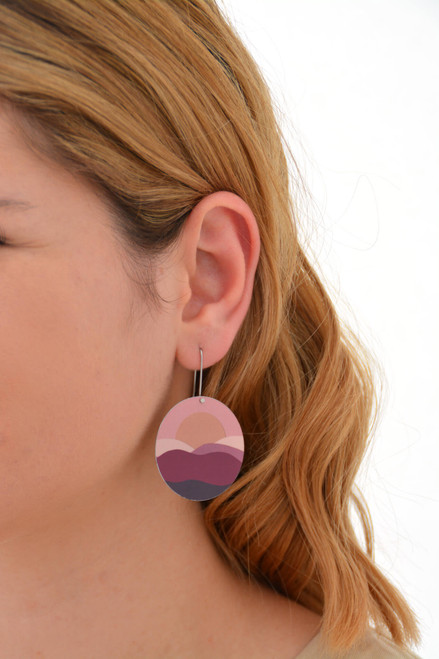 This is an image of a woman wearing a Kitty Came Home earring in her left ear. The flat circle is 36 millimetres in diameter and hands from a shepherds hook. The design is the night comes down by Satin and Tat. Magenta, burgundy and dusty pink shapes form an undulating landscape above which a golden sun sets in a terracotta sky.