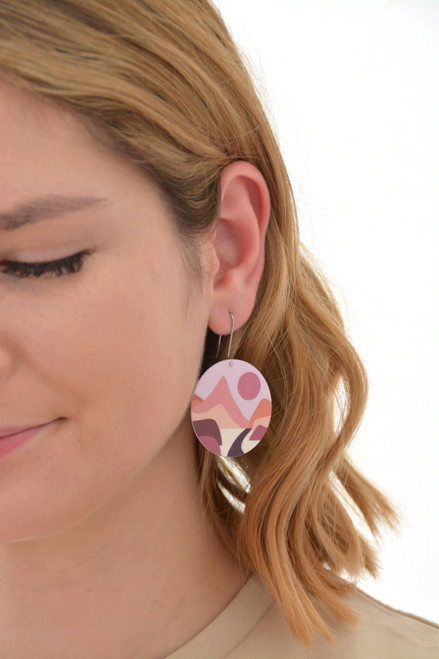 This is an image of a woman wearing a Kitty Came Home earring in her left ear. The flat circle is 36 millimetres in diameter and hangs from a shepherds hook. The design is lily of the valley by Satin and Tat. A terracotta coloured sinks in a pale pink sky towards a landscape of magenta, burgundy and pink hills. A path proceeds across the valley floor towards a cleft in the far mountain range.