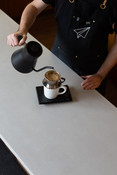 Barista using Fellow stagg pourover kettle with Kalita wave dripper and filter