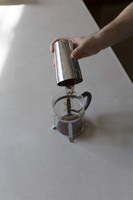 Barista hand pouring ground coffee in Timemore french press