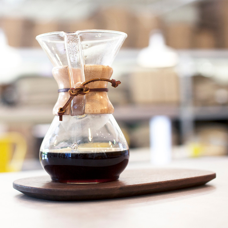 Chemex with brewed coffee on wood tray