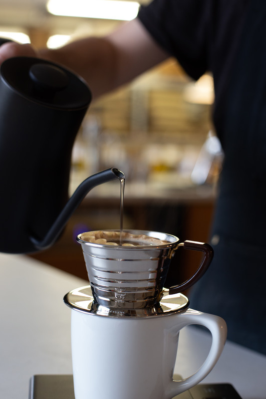 Close up of barista using Fellow stagg pourover kettle with Kalita wave dripper and filter