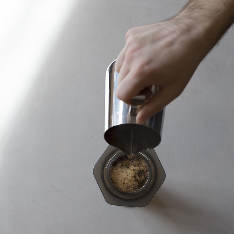 Bird's eye view of barista pouring water into Aeropress