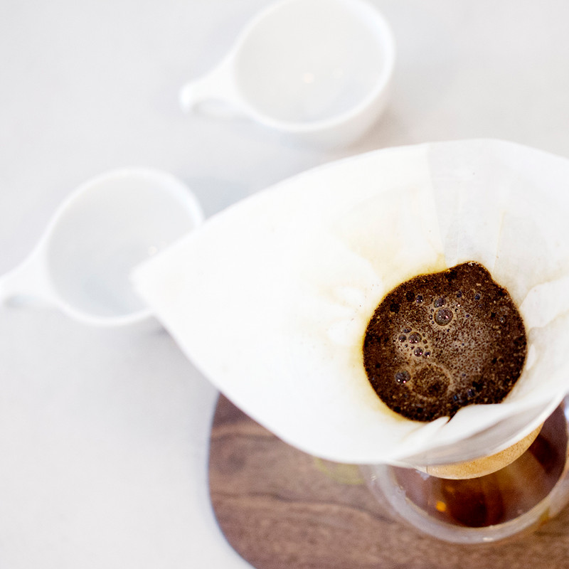 Bird's eye view of two cups and Chemex with coffee brewing