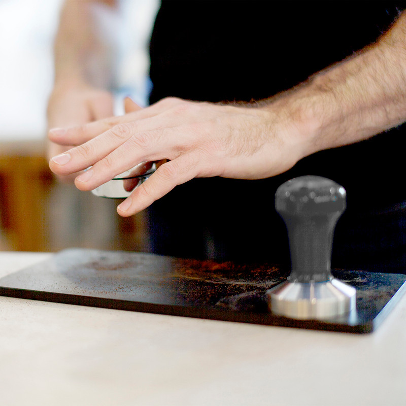 Barista preparing ground coffee in tamper