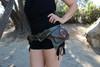 Green El Milagro Leather Utility Belt Bag female model with lifestyle shot wearing belt.