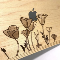 Custom maple wood MacBook cover with flower design.