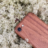 iPhone 8 in walnut, lifestyle with moss.