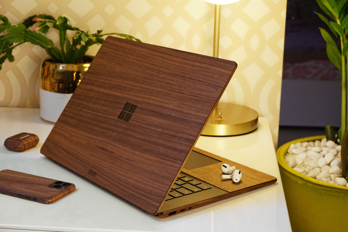 Toast wood cover for Surface Laptop in walnut, lifestyle.