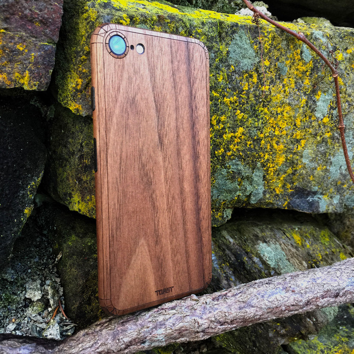 iPhone 8 in walnut, lifestyle with rocks.