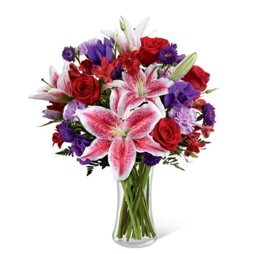 A gathering vase of stargazer lilies, roses, alstromeria, and lavender accent flowers. Nice and full