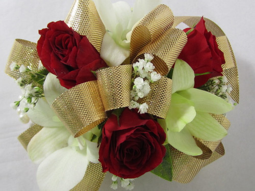 Shimmer and Shine with this beautiful, delicate wrist corsage designed exclusively by Chappell's Florist with red miniature spray roses and white orchids and a shimmering gold bow.