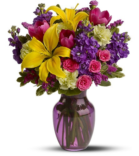 A mix of fresh flowers such as Asiatic lilies, tulips, stock and spray roses – in shades of yellow, pink, purple and green – is delivered in a glass vase.