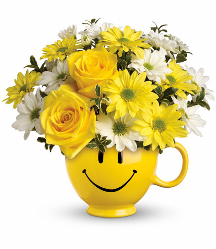 Yellow roses and daisy spray chrysanthemums along with white daisy spray chrysanthemums and oregonia are delivered in the one and only Be Happy® mug.
