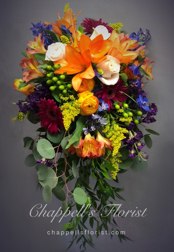 Beautiful Cascade of nice field mixture. Bouquet includes orange lilies, magenta gerbera daisies, orange raniculus, Silver dollar eucalyptus. blue delphinium, solidaster and more. Call for pricing